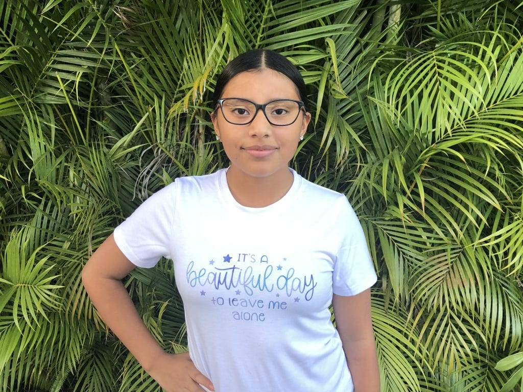 Girl standing in front of palm branches wearing shirt made with Cricut Infusible Ink that says It's a beautiful day to leave me alone